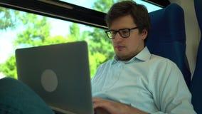 Ung affärsman som arbetar med bärbara datorn på drevet och att le stock video
