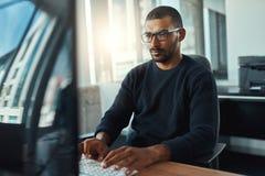 Ung affärsman som arbetar på arbetsplatsen arkivfoto