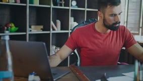 Ung affärsman som arbetar på bärbara datorn i inrikesdepartementet Modern chef arkivfilmer