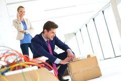 Ung affärsman som arbetar på bärbara datorn medan kvinnlig kollega som använder mobiltelefonen i nytt kontor Royaltyfri Bild