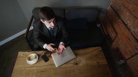 Ung affärsman som arbetar på bärbara datorn och talar med klienten, på tabellen på kafét Top beskådar stock video