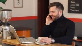 Ung affärsman som arbetar på en coffee shop med en bärbar dator och talar på telefonen lager videofilmer