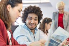 Ung affärsman som diskuterar med affärskvinnan med kollegor i bakgrund på kontoret arkivfoto