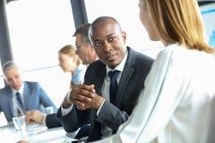 Ung affärsman som diskuterar med den kvinnliga kollegan i mötesrum Royaltyfria Foton