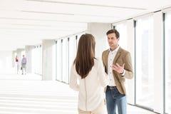 Ung affärsman som diskuterar med den kvinnliga kollegan i nytt kontor Royaltyfri Bild