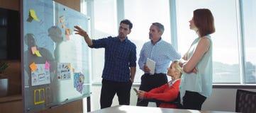Ung affärsman som diskuterar med kollegor på kontoret arkivbilder