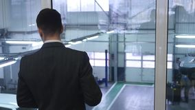 Ung affärsman som dricker kaffe och ser ut ur fönster stock video