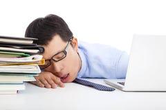 Ung affärsman som för är uttröttad till sovande på skrivbordet royaltyfri fotografi