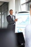 Ung affärsman som förklarar grafen, medan ge presentation i regeringsställning Arkivbilder