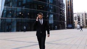 Ung affärsman som går, genom att använda telefonen i affärsområde arkivfilmer