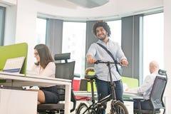 Ung affärsman som går med cykeln medan kollegor som i regeringsställning arbetar royaltyfri fotografi
