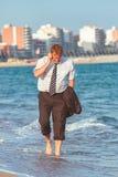 Ung affärsman som går på stranden för th e efter arbetstiden royaltyfri bild