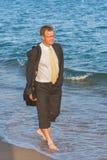 Ung affärsman som går på stranden för th e efter arbetstiden arkivfoton