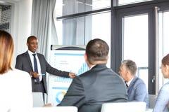 Ung affärsman som ger presentation till kollegor i bräderum Arkivbild