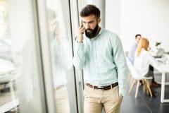 Ung affärsman som i regeringsställning använder mobiltelefonen Arkivbild