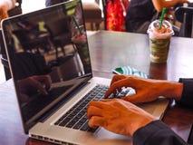Ung affärsman som i regeringsställning arbetar med bärbara datorn Arkivfoto