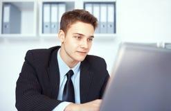 Ung affärsman som i regeringsställning arbetar på bärbara datorn arkivfoton