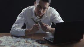 Ung affärsman som i regeringsställning räknar pengarsammanträde på tabellen Begrepp av lönen eller vinst arkivfilmer