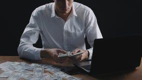 Ung affärsman som i regeringsställning räknar pengarsammanträde på tabellen Begrepp av lönen eller vinst stock video