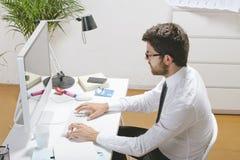 Ung affärsman som i regeringsställning skriver en dator. royaltyfri bild
