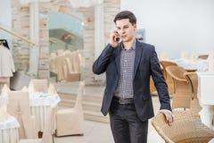 Ung affärsman som i regeringsställning står och talar på telefonen Y Arkivfoton