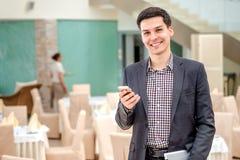 Ung affärsman som i regeringsställning står och talar på telefonen Y Royaltyfria Foton