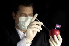 Ung affärsman som injicerar kemikalieer in i ett äpple med den kambodjanska flaggan Arkivfoton