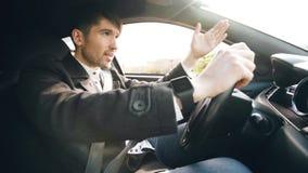 Ung affärsman som kör bilen som mycket är uppriven och som är stressad efter hårt fel och inflyttningtrafikstockning Arkivbilder