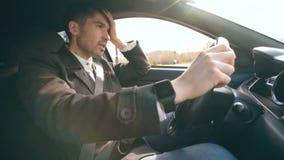 Ung affärsman som kör bilen som mycket är uppriven och som är stressad efter hårt fel och inflyttningtrafikstockning lager videofilmer