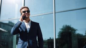 Ung affärsman som kallar på telefonen som står near kontorsbyggnad Stilig ung affärsman i solglasögon som talar på lager videofilmer