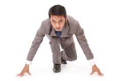 Ung affärsman som knäfaller som om omkring att starta ett lopp Royaltyfri Foto