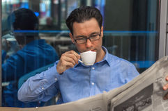 Ung affärsman som läppjar kaffe och den läs- tidningen på kafét arkivfoto