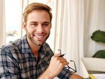 Ung affärsman som ler på kameran på arbete Arkivfoto