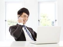 Ung affärsman som lyckligt i regeringsställning talar vid den smarta telefonen Royaltyfri Fotografi
