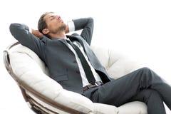 Ung affärsman som mediterar i stor bekväm fåtölj royaltyfri bild