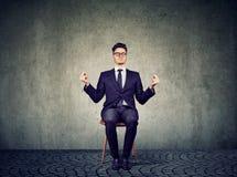 Ung affärsman som mediterar på stol arkivfoton