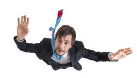 Ung affärsman som ner faller i fritt fall bakgrund isolerad white royaltyfri bild
