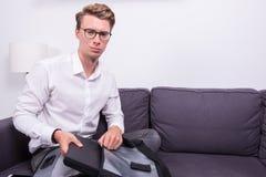Ung affärsman som packar hans påse på soffan Arkivfoton