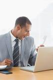 Ung affärsman som ropar in i telefonen på kontoret Arkivbild