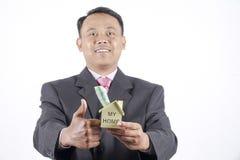 ung affärsman som rymmer en husmodell royaltyfri foto
