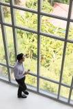 Ung affärsman som rymmer en kopp kaffe som står fönsterloen royaltyfri bild