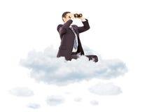 Ung affärsman som ser till och med kikare som placeras på molnet arkivfoto