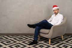 Ung affärsman som sitter på stol i den santa hatten, medan borra partiet för nytt år i kontoret arkivfoton