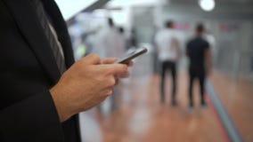 Ung affärsman som smsar på smartphonen, medan stå i köen, moderna grejer arkivfilmer