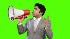 Ung affärsman som talar in i en megafon på grön bakgrund lager videofilmer