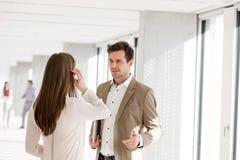 Ung affärsman som talar med den kvinnliga kollegan i nytt kontor Royaltyfria Foton