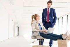 Ung affärsman som talar med den kvinnliga kollegan som använder bärbara datorn i nytt kontor Royaltyfria Foton