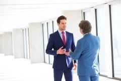 Ung affärsman som talar med den manliga kollegan i nytt kontor arkivfoto
