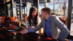 Ung affärsman som talar med egen psykolog på kafétabellen lager videofilmer