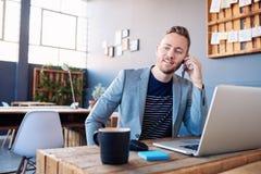 Ung affärsman som talar på hans mobiltelefon och använder en bärbar dator fotografering för bildbyråer